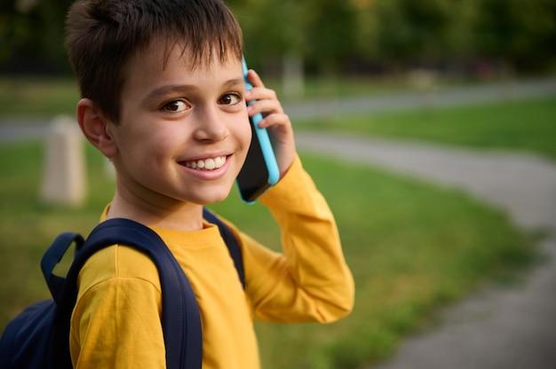 Retrato em close-up de um colegial adorável e amigável, vestindo um moletom amarelo falando no celular, sorrindo com um sorriso cheio de dentes, olhando para a câmera no fundo do parque da cidade