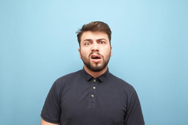 Retrato em close-up de um homem emotivo com barba, rosto surpreso e zangado