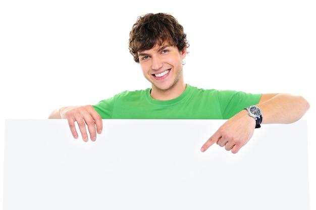 Retrato em close-up de um homem feliz sob uma faixa em branco e mostrando com o dedo