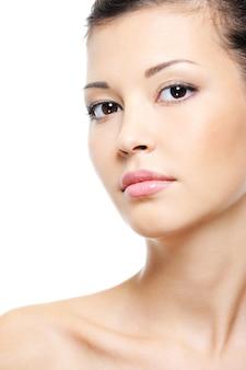 Retrato em close-up de um rosto feminino asiático atraente e sereno sobre branco