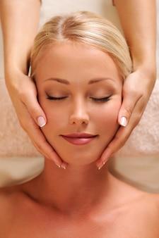 Retrato em close-up de um rosto feminino bonito recebendo massagem relaxante na cabeça