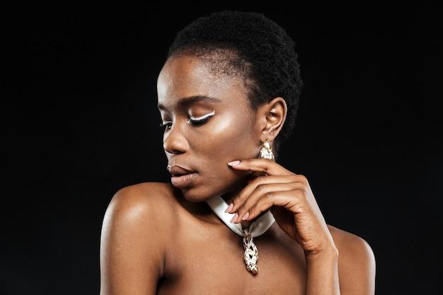 Retrato em close-up de uma bela e atraente mulher étnica isolada na parede preta