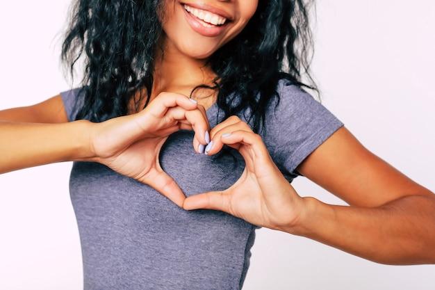 Retrato em close-up de uma garota afro-étnica contente com cabelos negros e bagunçados em pé e sorrindo amplamente, com as palmas das mãos perto do peito mostrando uma mão em forma de coração