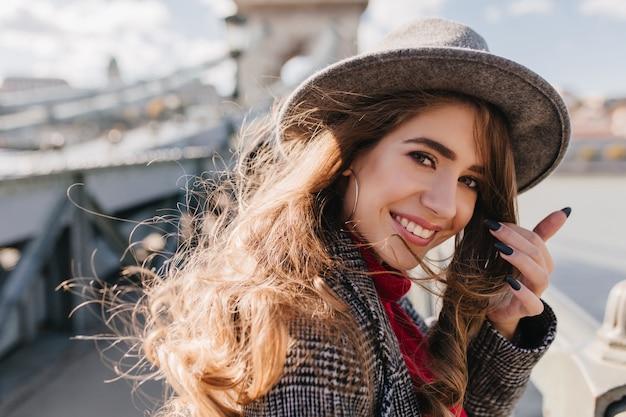 Retrato em close-up de uma garota branca em êxtase usando brincos fofos e um chapéu cinza estiloso