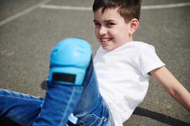Retrato em close-up de uma linda criança com joelheiras protetoras, sentada no asfalto de um campo esportivo na rua