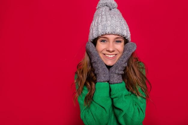 Retrato em close-up de uma linda garota feliz usando boné cinza de inverno, pulôver verde e luvas de mãos dadas no rosto e posando para a câmera com um sorriso incrível