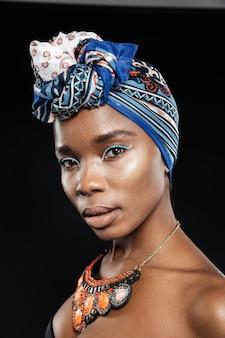 Retrato em close-up de uma linda mulher com xale na cabeça isolada na parede preta