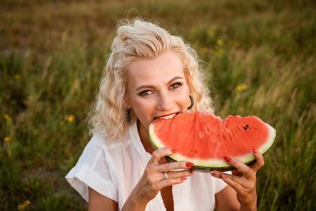 Retrato em close-up de uma mulher mordendo uma melancia na natureza