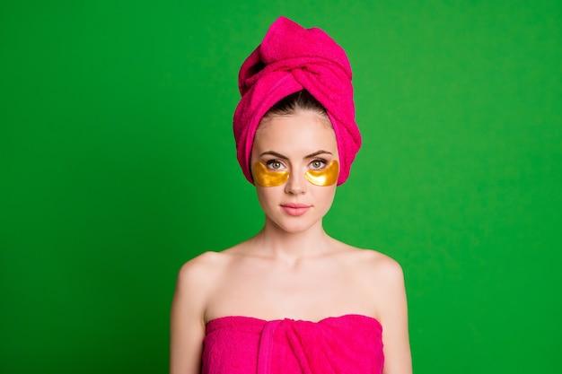 Retrato em close-up de uma senhora simpática e atraente usando turbante, aplicando manchas naturais douradas sob os olhos, isoladas em um fundo de cor verde viva