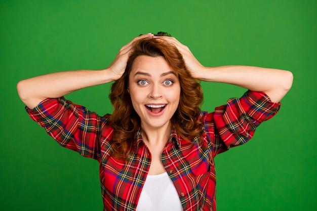 Retrato em close-up dela, ela é legal, atraente, muito espantada, oprimida alegre, alegre, garota de cabelos ondulados vestindo uma camisa xadrez.