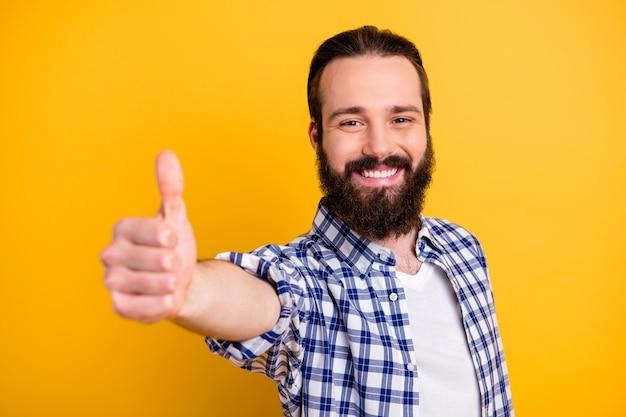 Retrato em close-up dele, ele é simpático, atraente, alegre, barbudo, cara de camisa xadrez, mostrando o polegar para cima