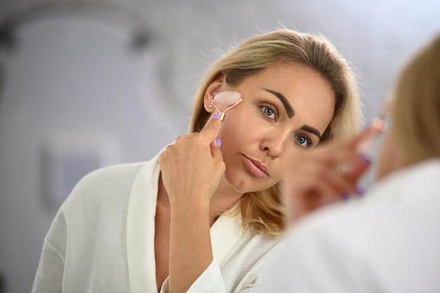 Retrato em close-up do rosto de uma linda mulher loira usando um massageador de pedra de rolo de jade para fazer uma massagem facial de drenagem linfática