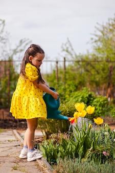 Retrato em comprimento total de uma menina regando flores de um regador de jardim no quintal um pouco g ...