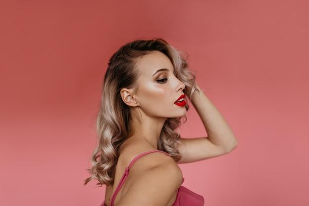 Retrato em perfil em estúdio de uma bela jovem loira com cabelos cacheados e lábios pintados de rosa, posando para a câmera, mostrando seus tenros ombros femininos