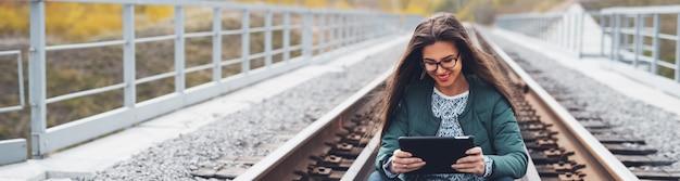 Retrato em perspectiva panorâmica de sorridente adolescente sentado na ferrovia e usando tablet digital inteligente. usando óculos e jaqueta verde.