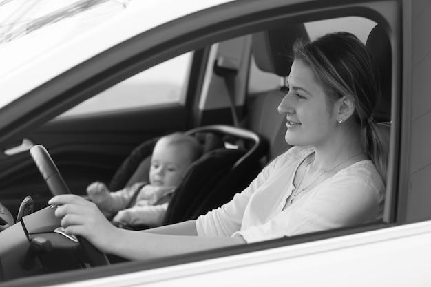 Retrato em preto e branco da mãe dirigindo o carro com o filho pequeno sentado na cadeira de segurança