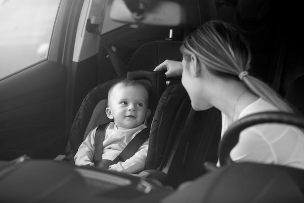 Retrato em preto e branco da mãe olhando para o bebê sentado no banco da frente do carro
