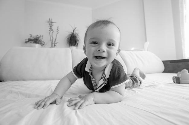 Retrato em preto e branco de adorável bebê sorridente engatinhando na cama no quarto
