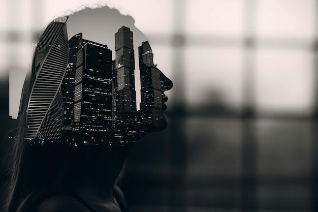 Retrato em preto e branco de dupla exposição da silhueta de uma mulher dentro de um prédio alto urbano de arranha-céus