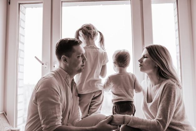 Retrato em preto e branco de família caucasiana olhando pela janela