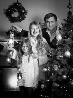 Retrato em preto e branco de família feliz posando para a árvore de natal com lanternas