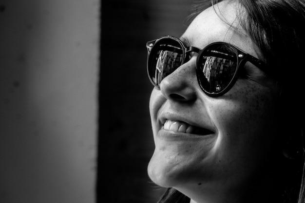 Retrato em preto e branco de mulher usando óculos escuros