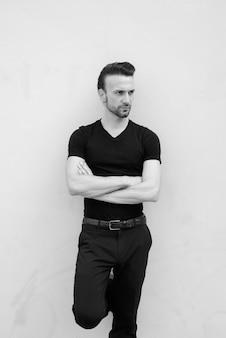 Retrato em preto e branco de um belo homem italiano com os braços cruzados pensando