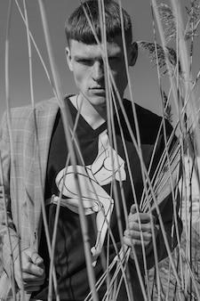 Retrato em preto e branco de um cara em uma camiseta preta estampada e jaqueta xadrez cinza segurando grama seca.