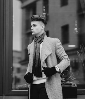 Retrato em preto e branco de um homem com um casaco de outono e luvas