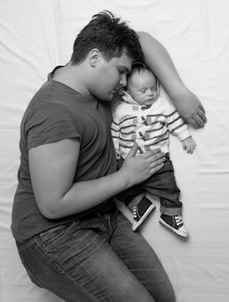 Retrato em preto e branco de um jovem pai dormindo na cama com um filho recém-nascido