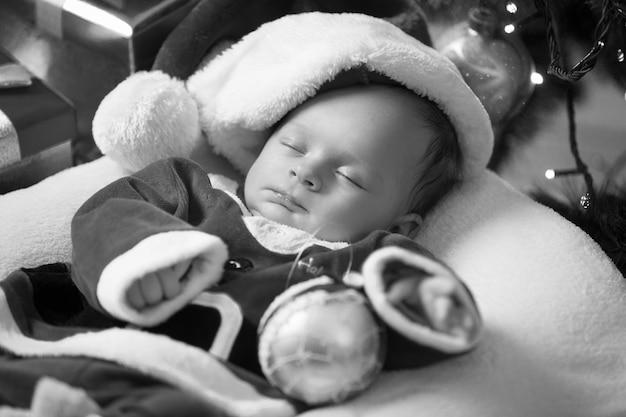 Retrato em preto e branco de um menino dormindo fantasiado de papai noel