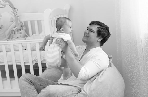 Retrato em preto e branco de um pai sorridente segurando seu filho bebê de 6 meses