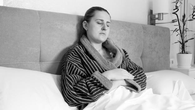 Retrato em preto e branco de uma jovem doente deitada na cama medindo a temperatura