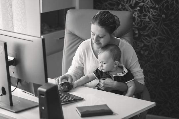 Retrato em preto e branco de uma jovem mãe sorridente, sentada no escritório com um bebê