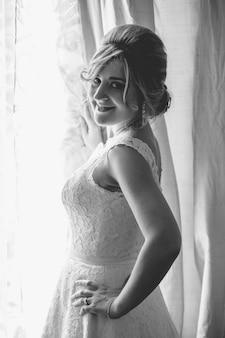 Retrato em preto e branco de uma jovem noiva elegante posando na janela de um quarto de hotel