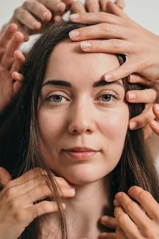 Retrato em preto e branco de uma linda garota com muitas mãos ao redor do rosto de uma mulher.