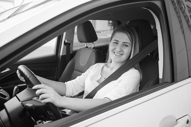 Retrato em preto e branco de uma mulher loira sorridente em uma camisa, dirigindo um carro