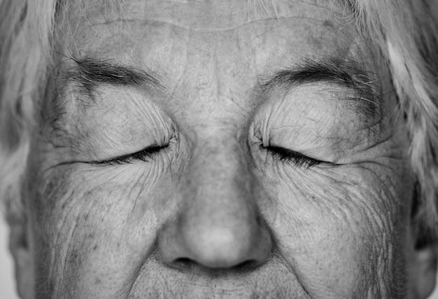 Retrato em preto e branco de uma senhora idosa branca de olhos fechados