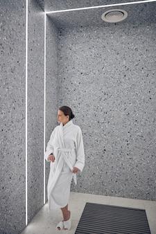 Retrato em tamanho real de uma senhora tranquila em um roupão atoalhado e chinelos olhando para a parede