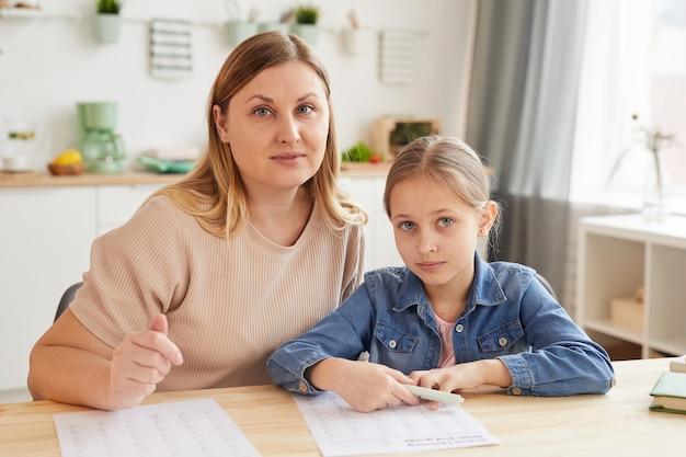 Retrato em tons quentes de mãe adulta ajudando a filha a fazer o dever de casa enquanto estudava em casa e olhando para a câmera
