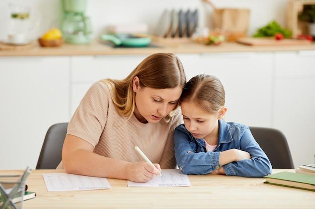 Retrato em tons quentes de mãe carinhosa ajudando a filha a fazer o dever de casa e estudar em casa em um interior aconchegante, copie o espaço