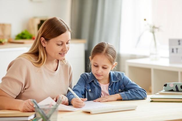 Retrato em tons quentes de mãe carinhosa ajudando a linda garota a fazer o dever de casa e estudar em casa em um interior aconchegante
