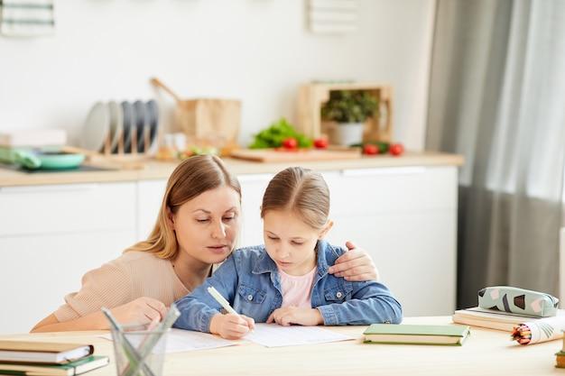 Retrato em tons quentes de mãe carinhosa ajudando a menina a fazer a lição de casa ou a estudar à mesa no interior de uma casa aconchegante, copie o espaço