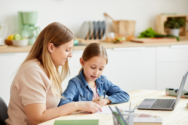 Retrato em tons quentes de mãe carinhosa ajudando linda garota fazendo a lição de casa ou estudando à mesa no interior aconchegante da casa, copie o espaço