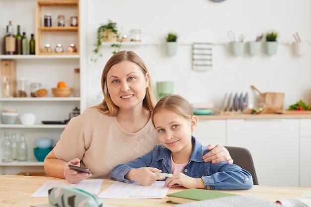 Retrato em tons quentes de mãe e filha felizes, sorrindo para a câmera enquanto estão sentadas na mesa juntas e estudando no interior da casa, copie o espaço