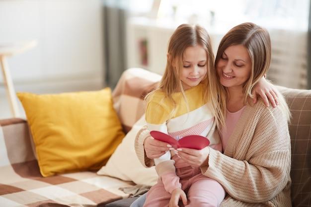 Retrato em tons quentes de mãe feliz abraçando a filha enquanto lê o cartão de natal no dia das mães, copie o espaço