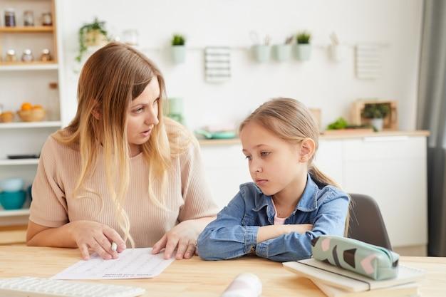 Retrato em tons quentes de mãe frustrada conversando com a menina enquanto faz a lição de casa ou estuda em casa, copie o espaço