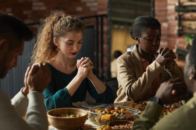 Retrato em tons quentes de um grupo multiétnico de jovens elegantes orando de olhos fechados enquanto estão sentados à mesa de jantar durante a celebração do dia de ação de graças.