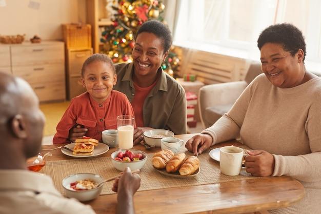 Retrato em tons quentes de uma família afro-americana feliz desfrutando de chá e lanches enquanto celebra o natal em casa
