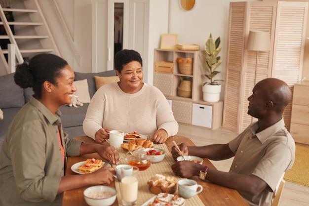 Retrato em tons quentes de uma família afro-americana feliz sentada à mesa de jantar enquanto toma o café da manhã em casa
